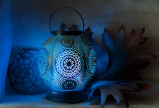 Aroma diffuser in the style of an ancient oriental lamp. still life with a diffuser, a catcher of dreams and maple leaves.