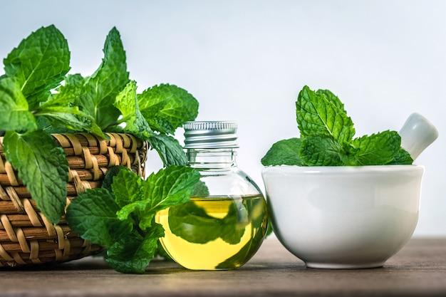 Ароматическое эфирное масло из перечной мяты в бутылке на столе со свежей зеленой мятой lea