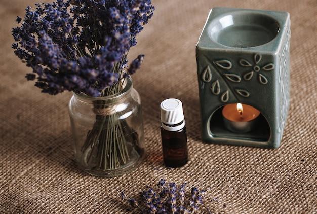 Аромалампа с ароматическим маслом и горящей свечой с ведром лаванды в стакане, концепция ароматерапии