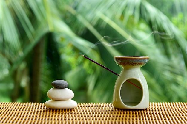 Ароматическая лампа с ароматической палочкой и камнями дзен на ротанговом столе на размытом зеленом фоне природы