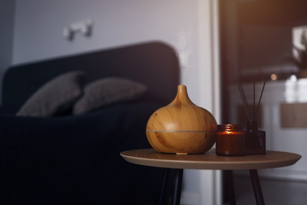寝室の木製テーブルにアロマオイルディフューザー、芳香剤、キャンドル。温かみのある雰囲気のある写真。