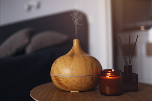 Aroma oil diffuser, air freshener and candle on a wooden table in the bedroom. warm, atmospheric photography.
