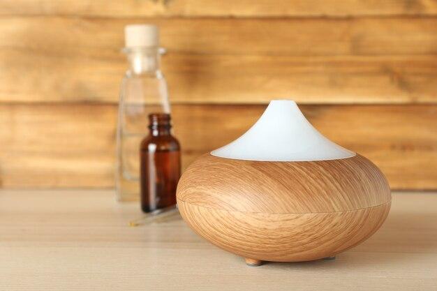 Распылитель ароматического масла на деревянных фоне