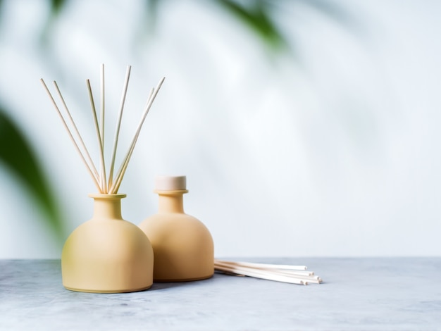 Aroma reed diffuser home fragrance with rattan sticks on a light background with palm leaves.