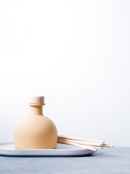 Aroma reed diffuser home fragrance with rattan sticks on a light background