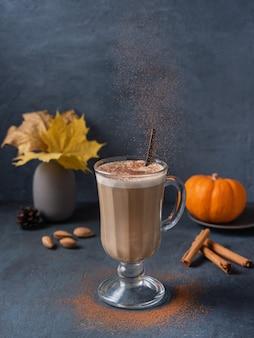 アロマスパイスパンプキンコーヒーラテドリンク、濃紺のテーブルにミルクフォーム、シナモン、チョコレート。白いマグカップのカカオココア。秋の朝。縦向きの画像
