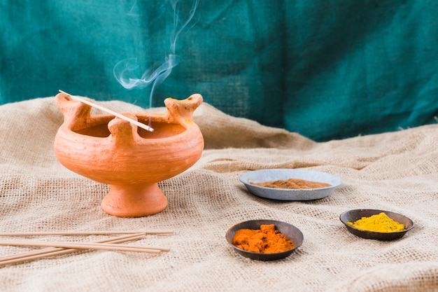 Aroma sticks on bowl near saucers with different spices