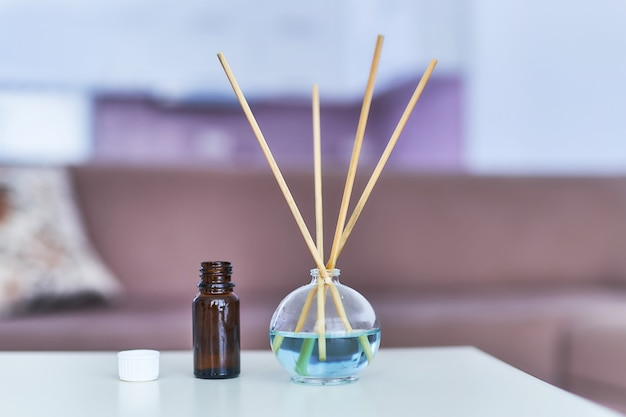 Aroma sticks and essential oil bottle in home interior