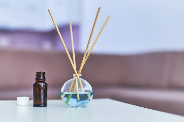 Aroma sticks and essential oil bottle in living room