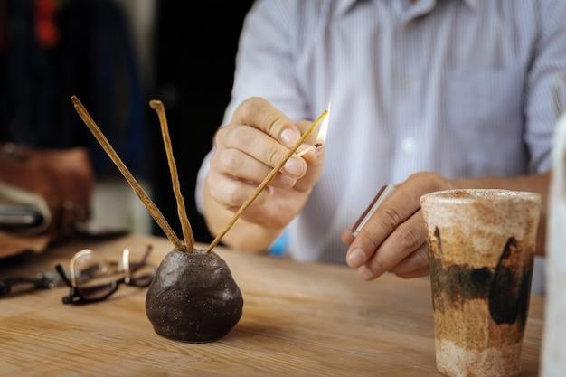 アロマスティック。茶色の木製のテーブルの上に立っている3つの小さな香りの棒を燃やすストライプのシャツを着た男