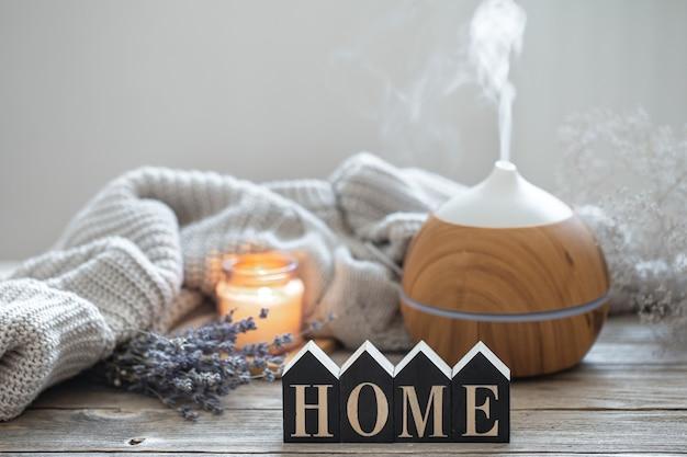Ароматный натюрморт с современным диффузором ароматического масла на деревянной поверхности с трикотажным элементом, уютными деталями и декоративным словом home.