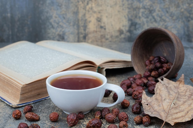 Ароматный чай в белой чашке с листом и книга на мраморном столе