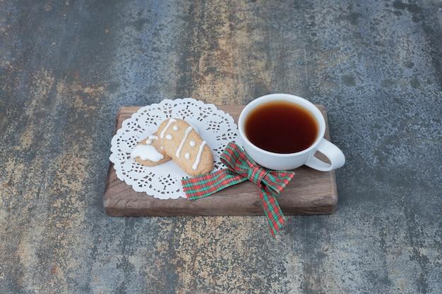 Tè aromatico in tazza bianca con biscotti di natale su tavola di legno.