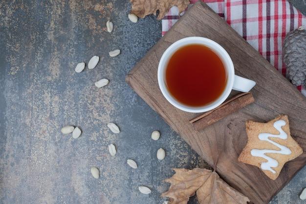 Tè aromatico in tazza bianca con biscotti e cannella su sfondo di marmo