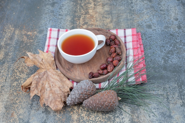 Tè aromatico in tazza bianca con cinorrodi e pigne nelle quali su sfondo marmo