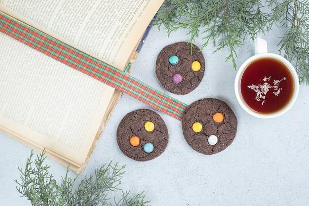 灰色の表面にチョコレートクッキーとハーブティーのアロマホワイトカップ