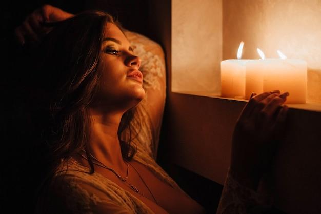下着姿のセクシーなブルネットのアロマテラピーは、就寝前のロマンチックな設定の前にキャンドルを消します