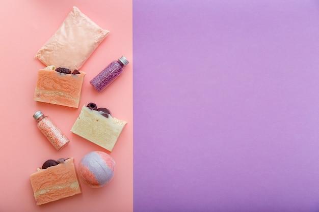 바디 스킨케어 웰빙을 위한 아로마 테라피 목욕 뷰티 화장품. 목욕 폭탄 비즈 천연 핑크 비누 바 오일 위생 세면도구. 텍스트 복사 공간이 있는 평평한 보라색 배경.