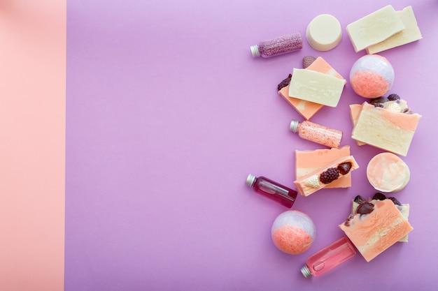 바디 스킨케어 웰빙을 위한 아로마 테라피 목욕 뷰티 화장품. 목욕 폭탄 비즈 천연 비누 오일 위생 세면도구. 텍스트 복사 공간이 있는 평평한 분홍색 보라색