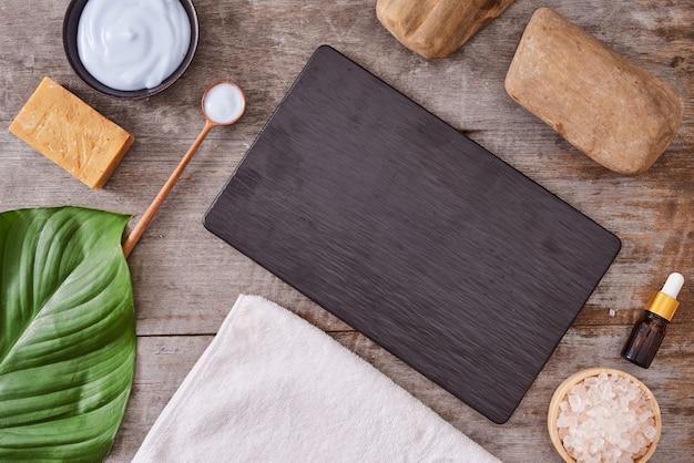 アロマテラピー:バスソルト、化粧品クリーム、有機石鹸、木製テーブルの緑の葉