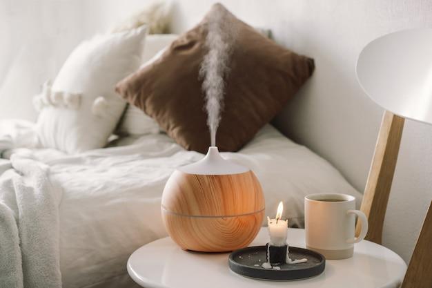 Концепция ароматерапии. распылитель ароматического масла на стуле напротив в спальне. освежитель воздуха. ультразвуковой ароматизатор для дома