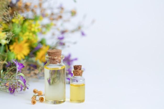 アロマセラピーエッセンシャルオイルのボトルと自然な漢方薬、癒しのハーブと白いテーブルの上の花。テキストのためのスペース