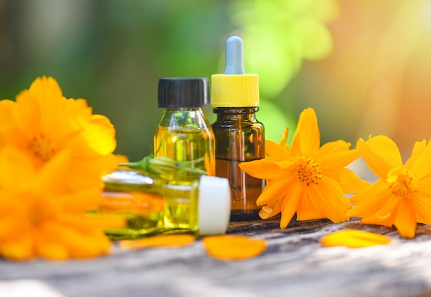 Aromatherapy herbal oil bottles aroma with flower yellow on nature green essential oils natural for face and body beauty remedies on wooden table and organic minimalist lifestyle