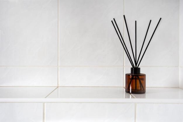 복사 공간이 있는 흰색 타일 벽 근처의 화장실이나 욕실에 있는 유리병에 아로마테라피 스틱