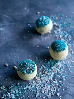 회색 배경에 에메랄드색 소금을 넣은 아로마 목욕 폭탄 에센셜 오일이 있는 목욕 소금