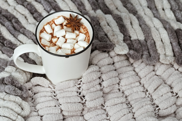 Aromatic cacao drink with marshmallows on cozy soft gray pompon yarn. holiday concept.top view.