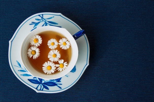 Aromatic chamomile tea in a cup and sauce on a dark placemat background. flat lay.
