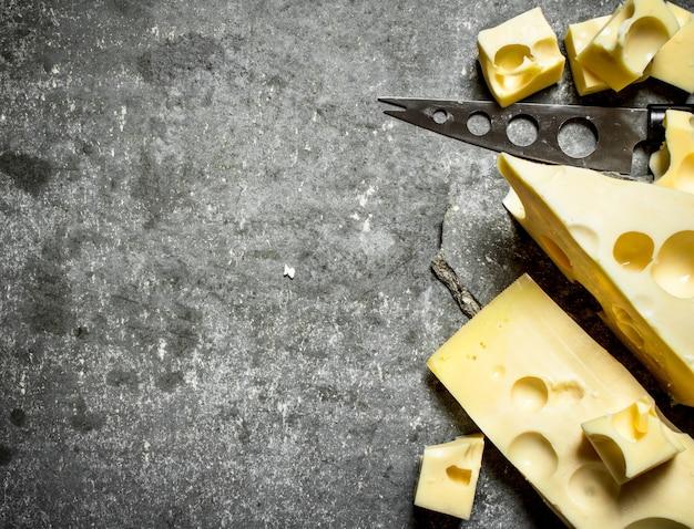칼로 향기로운 치즈. 돌 테이블에.
