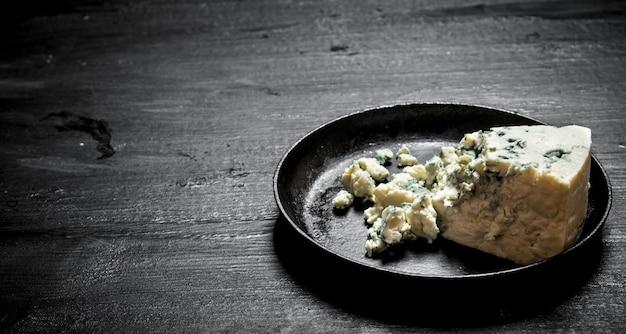 오래 된 접시에 파란색 곰팡이와 아로마 치즈. 검은 나무 배경.