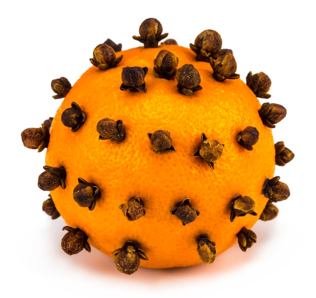 Aromatic christmas orange with cloves on white