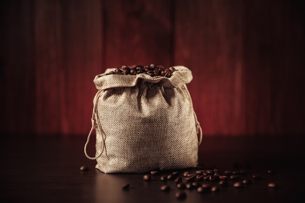 Aromatic coffee beans in bag isolated on wooden background.