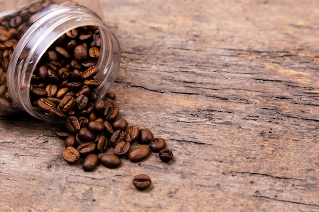 Aromatic coffee beans dropped out of a glass jar. banner background