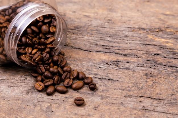 Ароматные кофейные зерна выпали из стеклянной банки. баннер фон