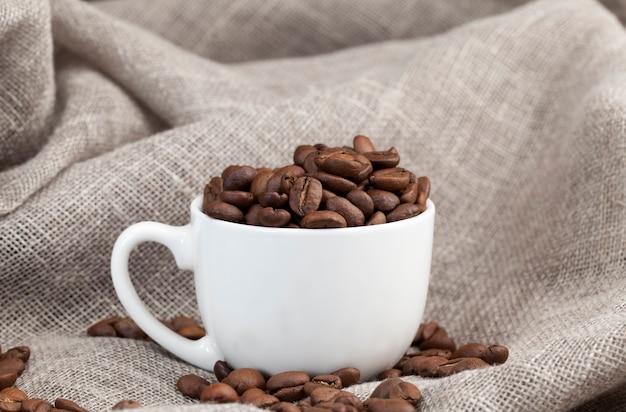 カップに入った芳香性のコーヒー豆、マグカップでおいしいコーヒーを作るためのコーヒー豆、飲み物のための全体の形のコーヒー豆、クローズアップ