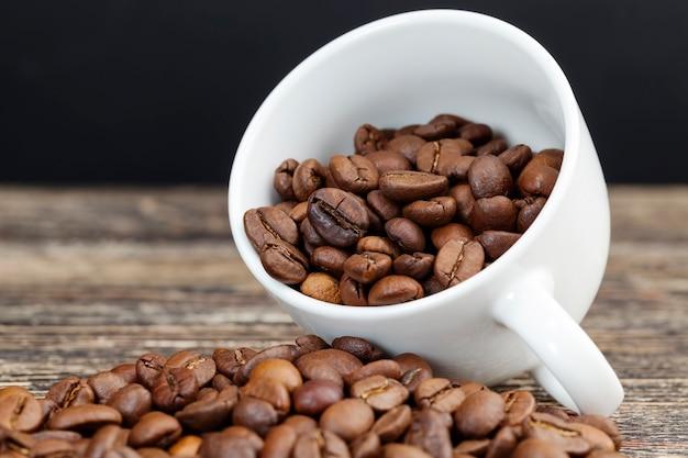 컵에 담긴 향기로운 커피 콩, 머그에 맛있는 커피를 만들기 위한 커피 콩, 음료를 위한 전체 형태의 커피 콩