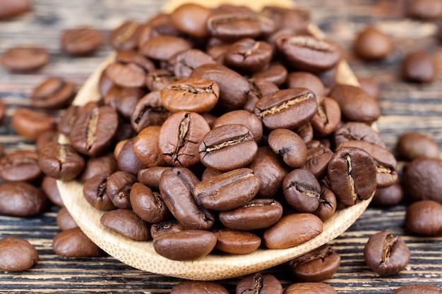 나무 숟가락에 있는 향기로운 커피 콩, 대나무로 만든 계량 숟가락에 맛있는 커피를 만들기 위한 커피 콩, 갈기 위한 전체 형태의 커피 콩, 클로즈업
