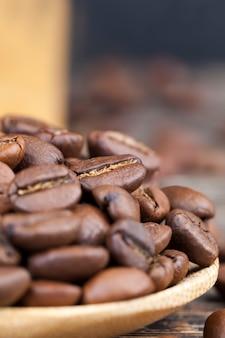 木のスプーンで芳香性のコーヒー豆