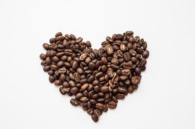 白い背景の上のハートの形の芳香族コーヒー豆