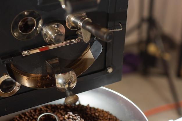 곡물 냉각기가 있는 현대적인 장비에 있는 향기로운 커피 콩. 산업 개념입니다. 콩을 굽는 데 사용되는 현대적인 기계. 냉각 실린더에 커피 로스터를 붓고 있습니다.