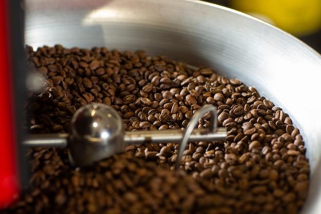穀物冷却装置を備えた最新の設備に配置された芳香性コーヒー豆。業界の概念。豆の焙煎に使用される最新の機械。冷却シリンダーに注がれているコーヒーロースター。
