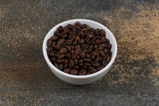 Aromatic coffee beans in white bowl.