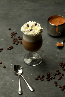 Aromatic coffee in a glass cup with whipped cream