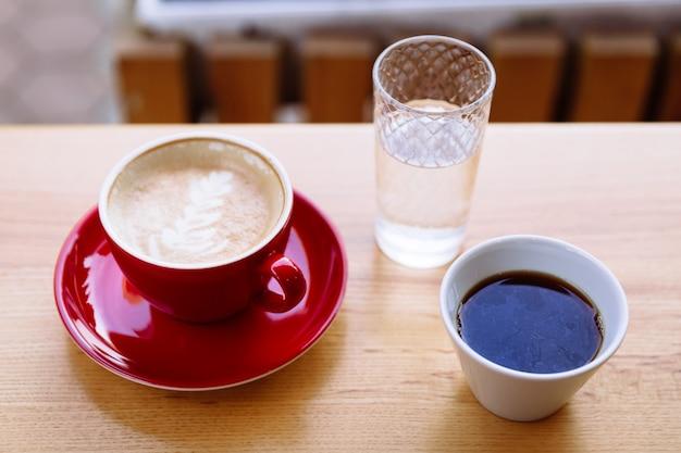 ミルクフォームとラテアートが入った赤いカップのアロマコーヒーと白いカップの淹れたてのコーヒー