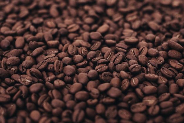 芳香族ダークブラウンコーヒー豆の背景上面図フィルムグレイン効果のある写真