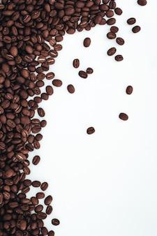 白い背景に分離された芳香族ダークブラウンコーヒー豆コピースペースの上面図