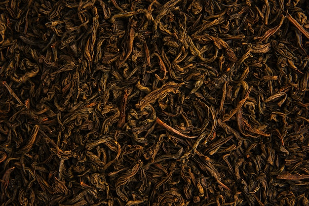 Aromatic dry green tea leaves with close-up.